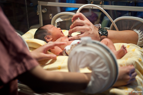 Newborn baby in incubator being examined by doctor