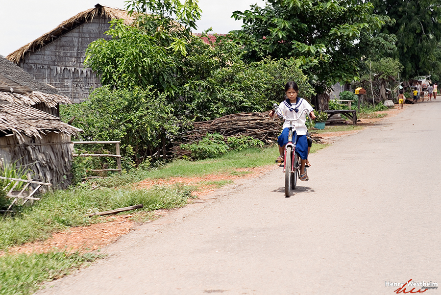 Cambodia, School girl riding bicycle, Siem Reap