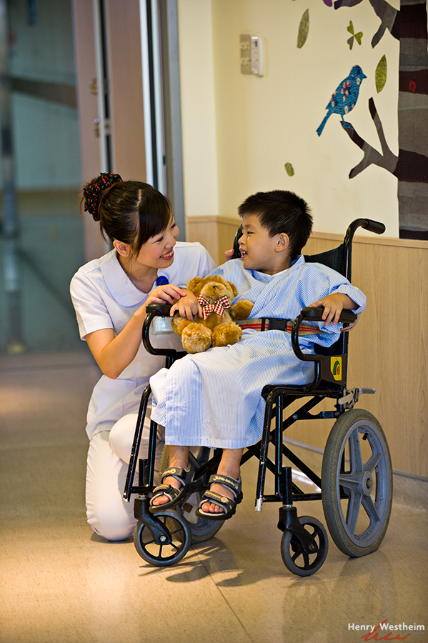 Nurse talking with young child patient in hospital