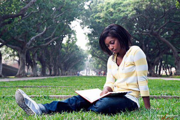Young woman reading outdoors on college campus