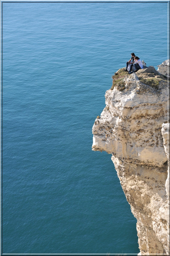 two persons at the top of a cliff over the sea