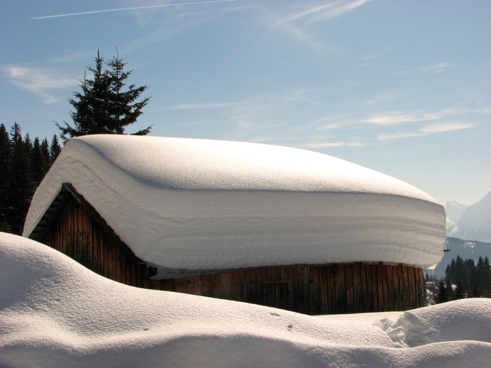 snow on the roof of a mountain chalet
