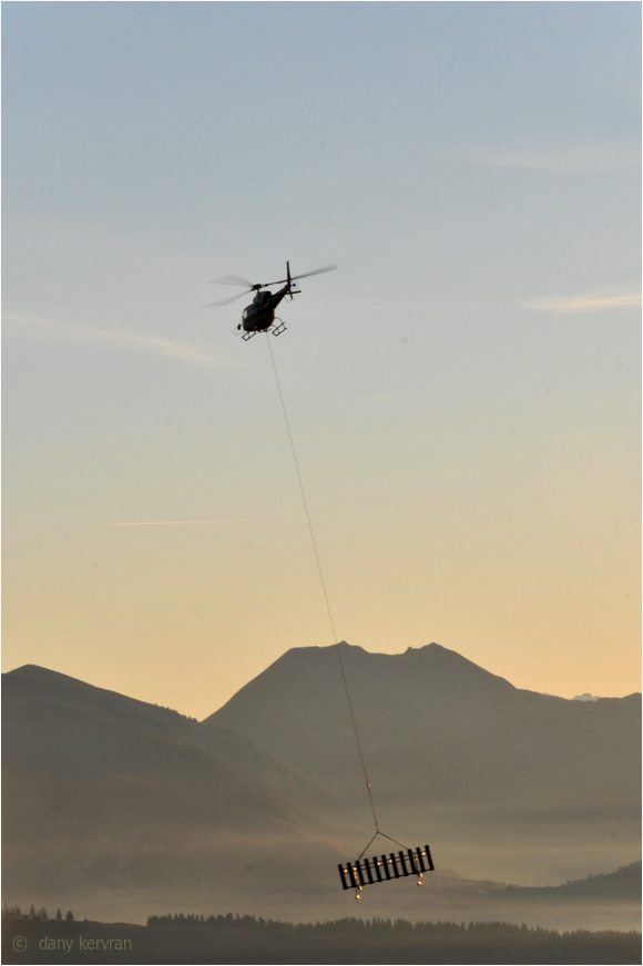an helicopter transports a metallic structure