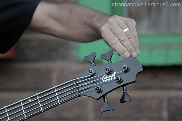 Bassist tuning his bass