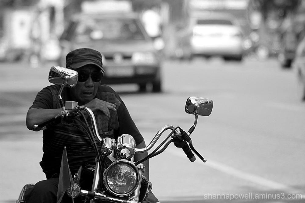 Man sitting on motorbike smoking