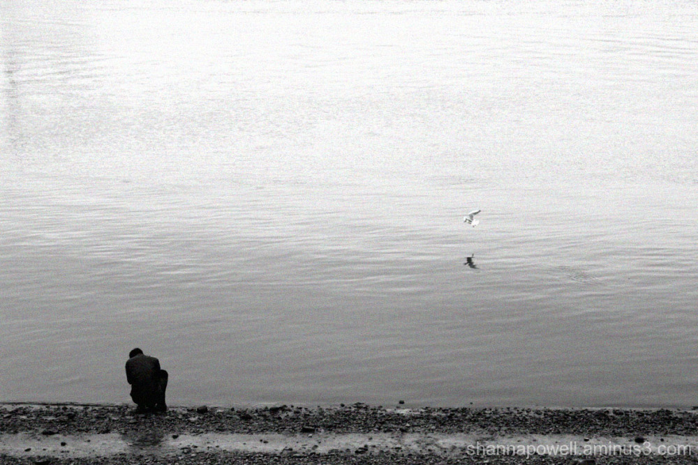 Man kneeling by river bank