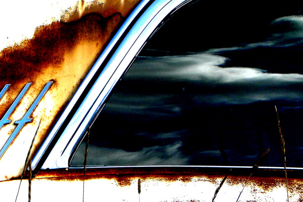 Rear window on old rusted car.