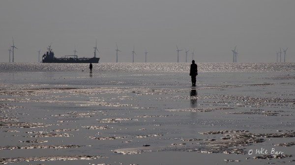 distant tanker passing Gormley sculptures on beach