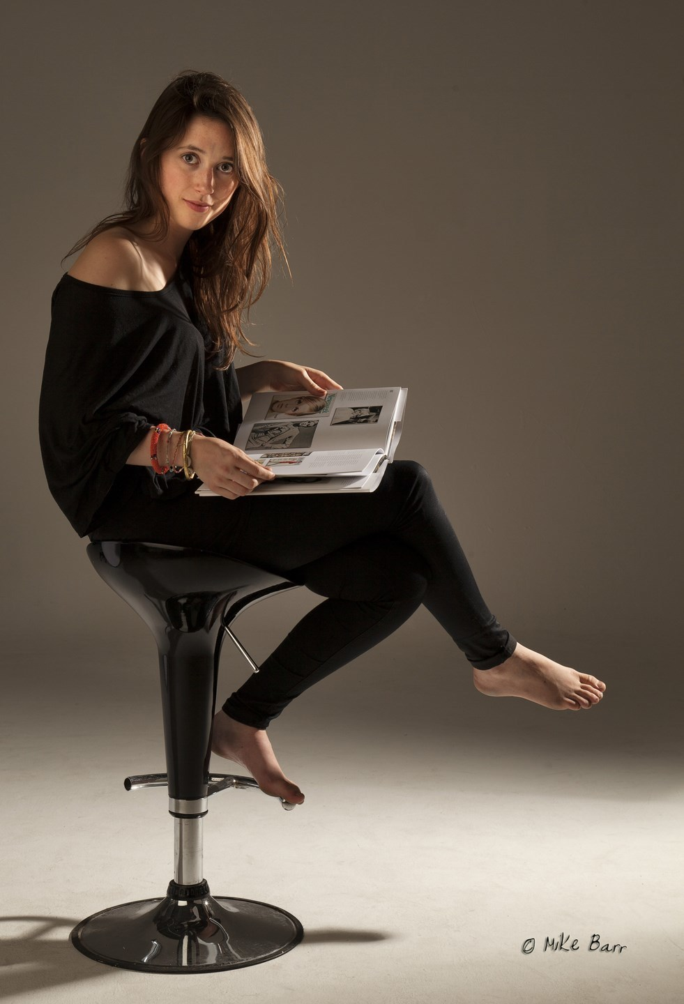 young woman on a barstool reading