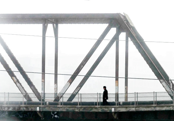 a man walking across a bridge in morning mist