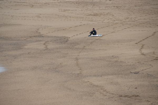 un surfer seul sur le sable