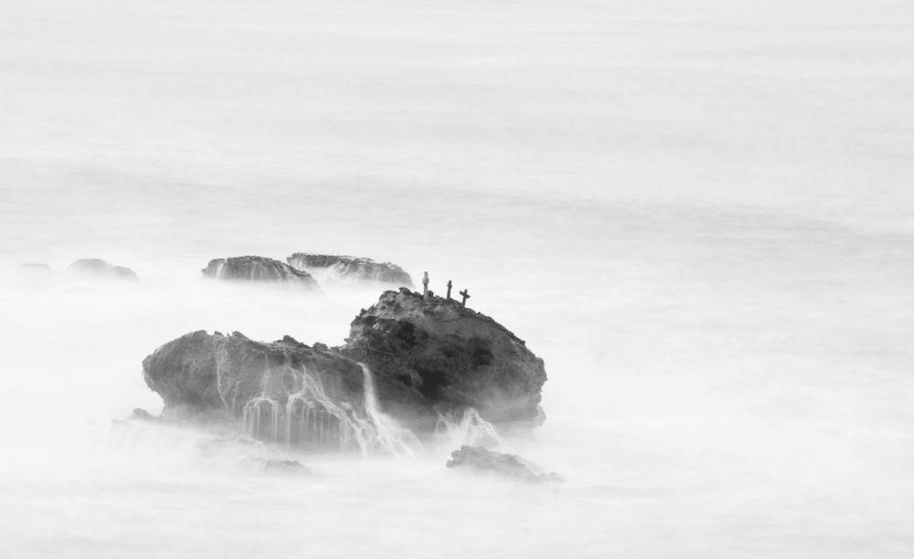 un rocher semble flotter sur la mer en pose longue