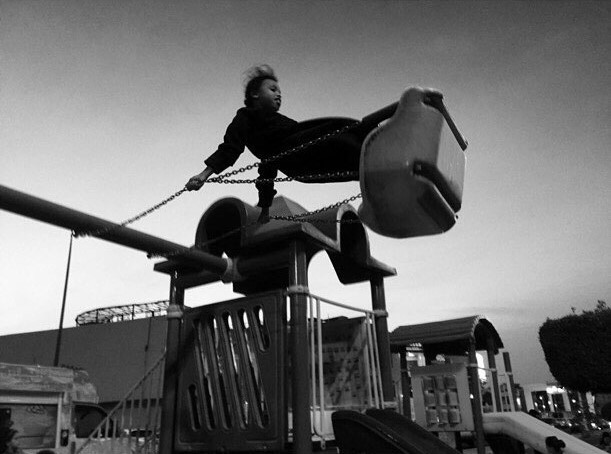a girl playing in a swing