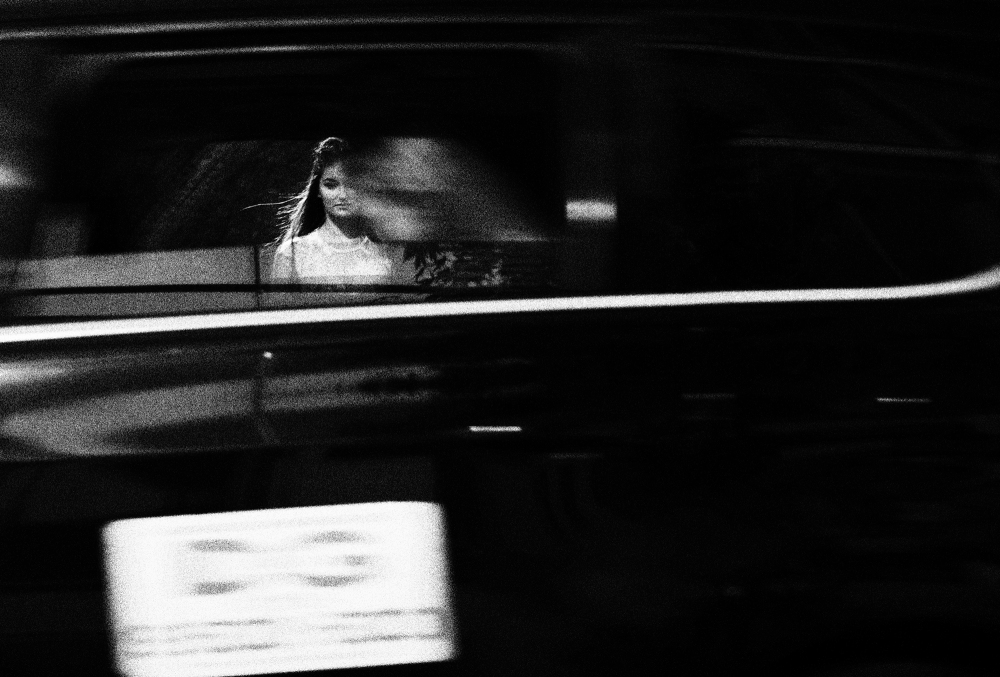 Girl looking through taxi window as it passes