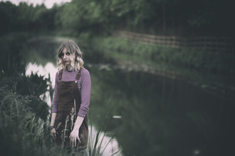 Girl by a river looking forlorn