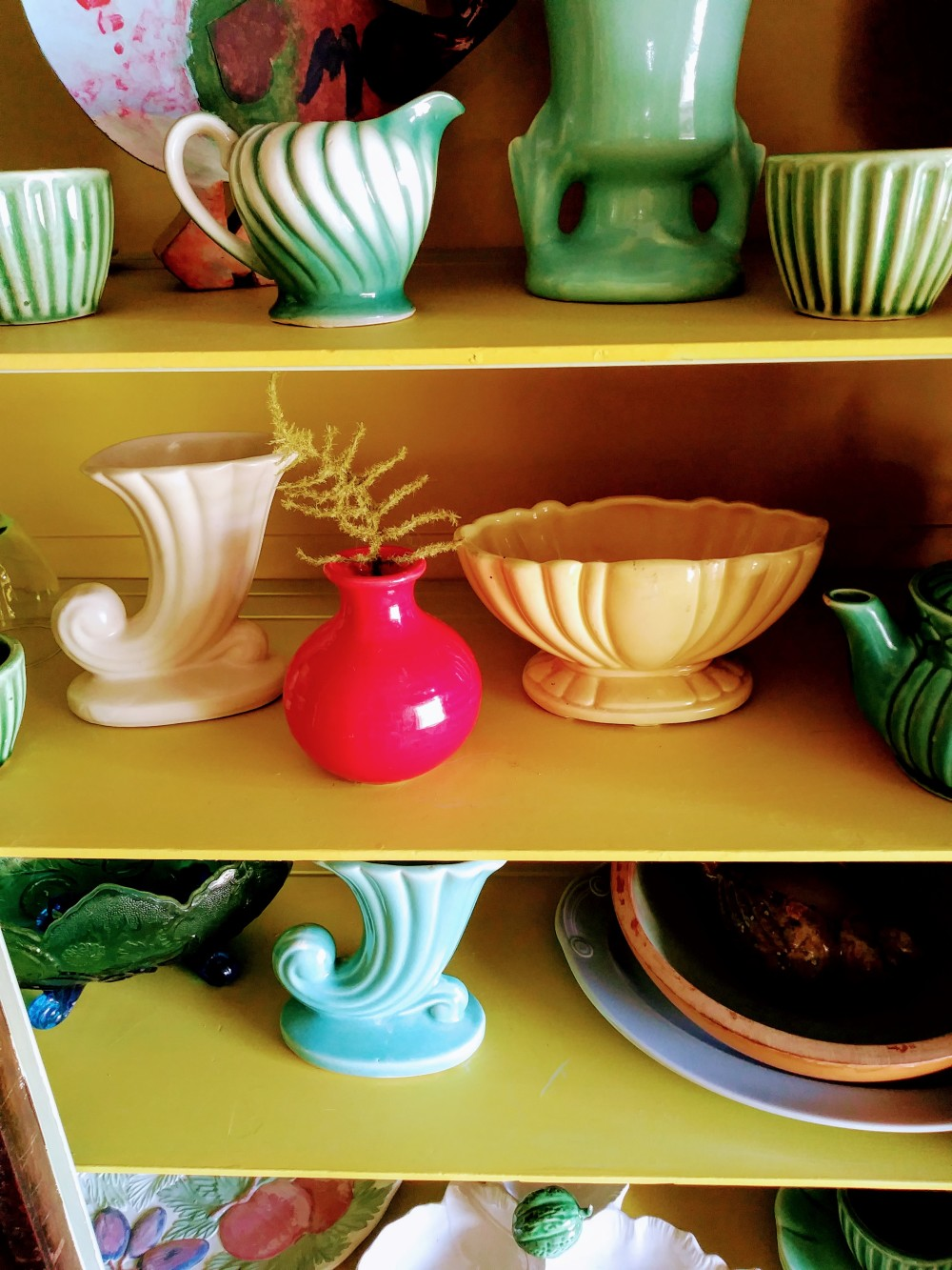 colorful collection of vintage pottery in cabinet