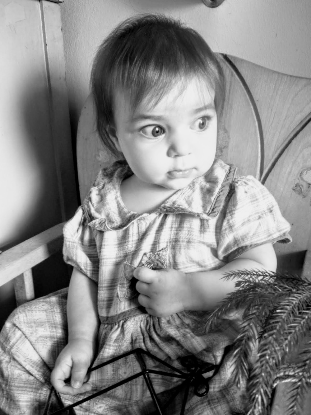 black n white baby girl in highchair with big eyes