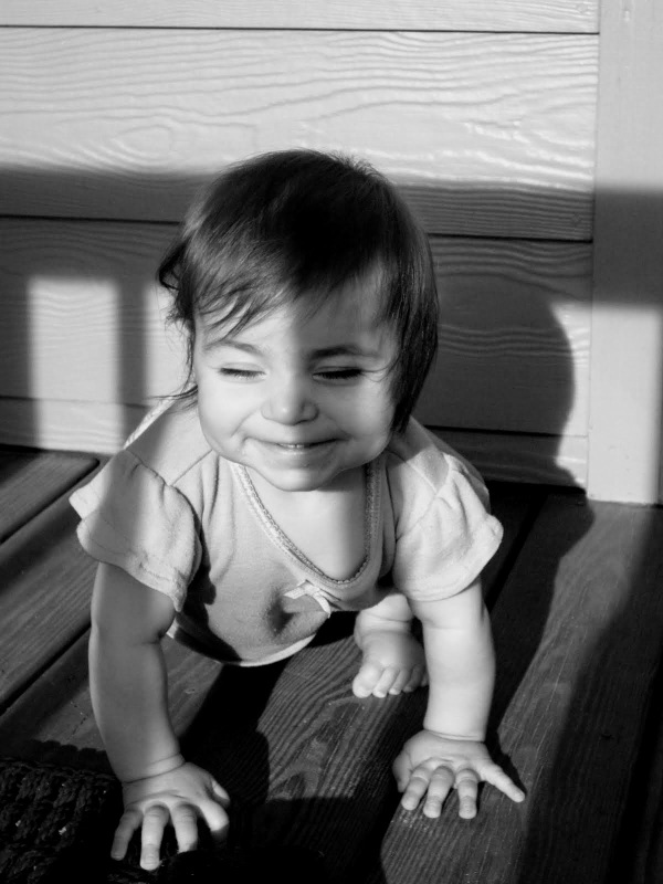 baby smiling in the sunshine, eyes closed crawling
