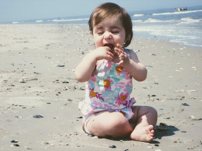sweet baby on beach tasting the sand