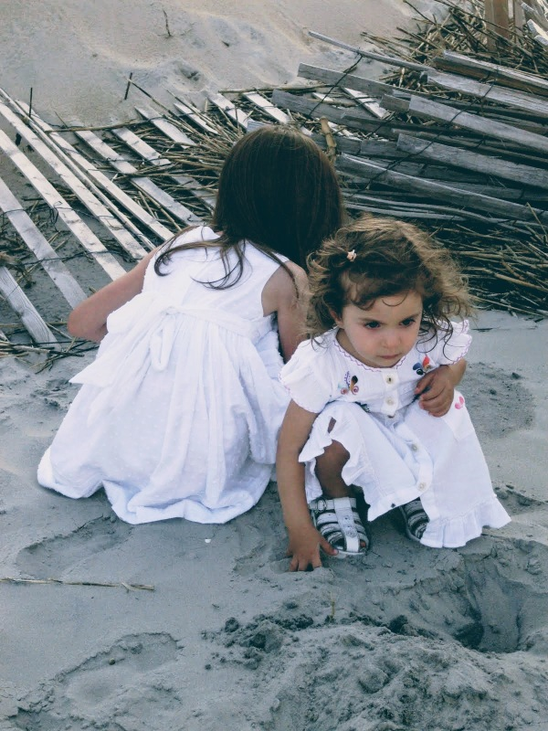 sweet girls on beach sand in white dresses curls