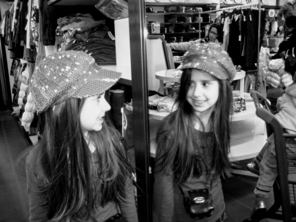 girl in black and white looking in mirror with hat