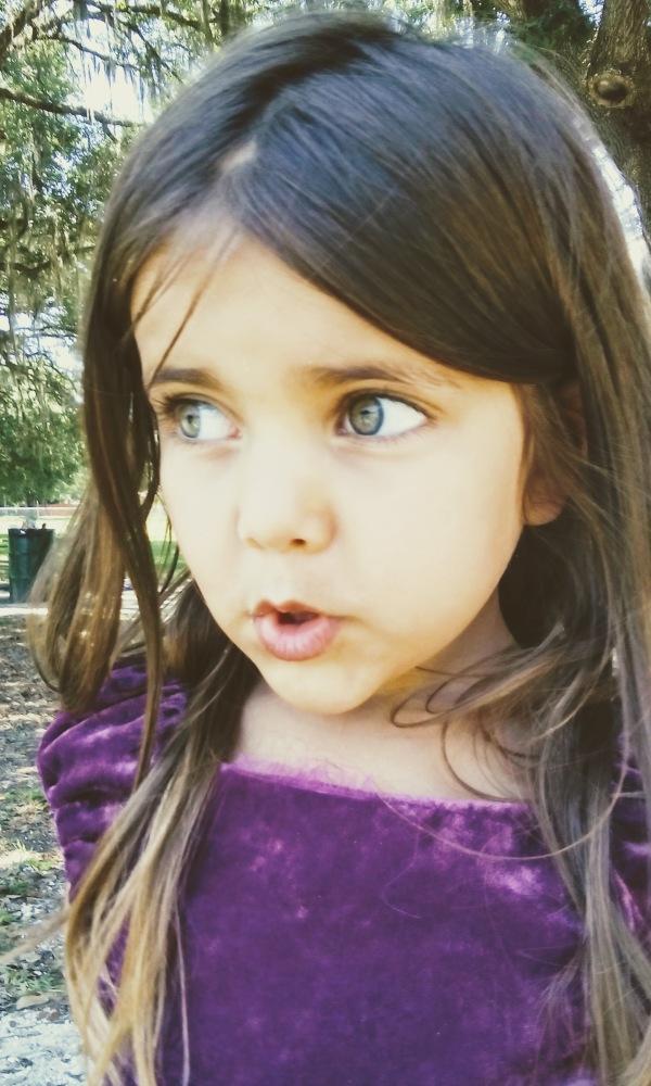 girl in purple dress wide green eyes puckered