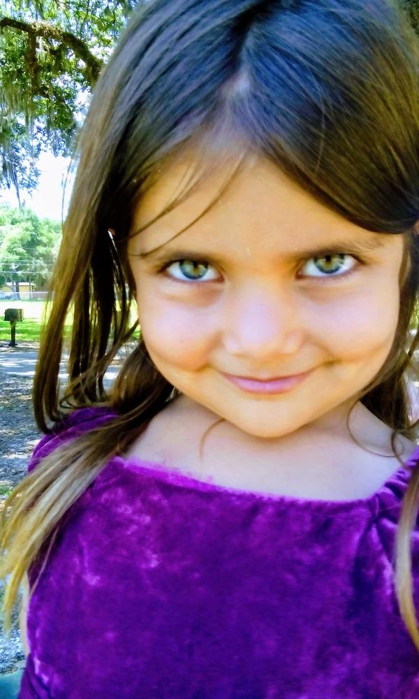 girl smile purple dress brown hair green eyes