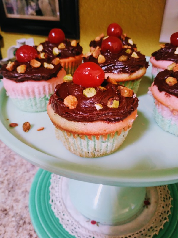 spumoni cupcakes with cherry on cake stand