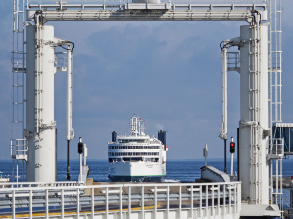 A ferry on its way framed by its departure station