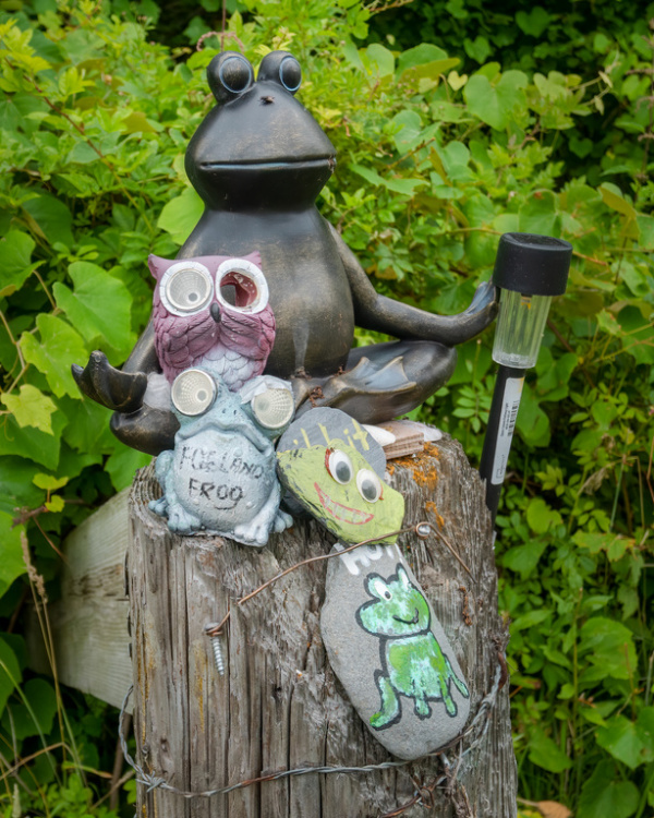 A frog lawn ornament that sits upon a fence post b