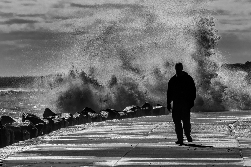 A person walks on a causeway with storm waves cras
