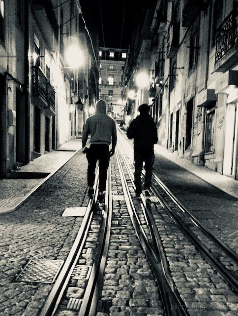Two men walk down a shadowy Lisbon street at night